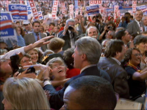 vídeos de stock e filmes b-roll de high angle medium shot tracking shot bill clinton shaking hands, hugging, and kissing members of convention crowd - 1992