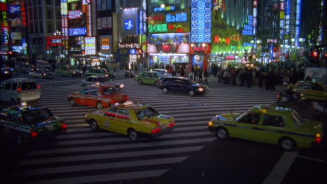 High angle medium shot traffic on busy street and pedestrians waiting at intersection / Tokyo, Japan