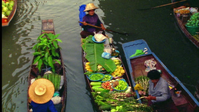 High angle medium shot two Asian women exchanging food from boats at floating market / Damneon Saduak, Thailand