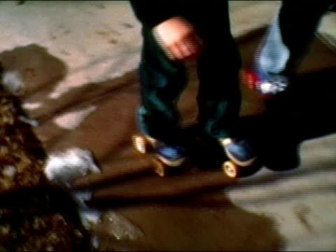 vídeos de stock, filmes e b-roll de 1983 high angle medium shot two boys roller skating on suburban sidewalk - braço humano