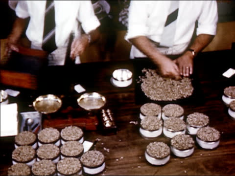 1954 high angle medium shot two men sorting coffee beans / audio - anno 1954 video stock e b–roll