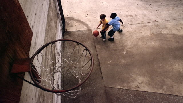 high angle medium shot two young boys playing one-on-one basketball / boys shooting ball - shooting baskets stock videos and b-roll footage