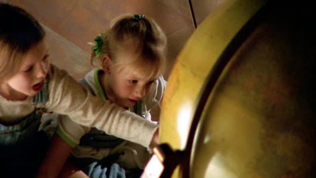 vídeos y material grabado en eventos de stock de high angle medium shot two young girls looking at a large globe and spinning it - globo terráqueo para escritorio
