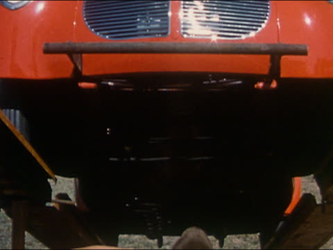 1959 high angle medium shot view of chassis of red hot rod rolling off transport trailer - one teenage boy only stock videos & royalty-free footage