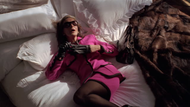 High angle medium shot woman falling onto bed next to fur coat / removing sunglasses and gloves / yawning + stretching