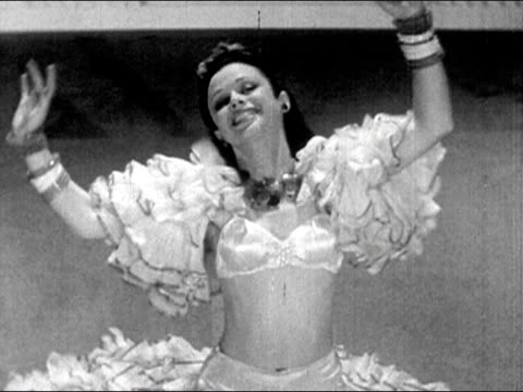 1941 High angle medium shot woman in ruffled dance outfit kneeling, leaning back, and shimmying while looking at camera with arms raised/ AUDIO