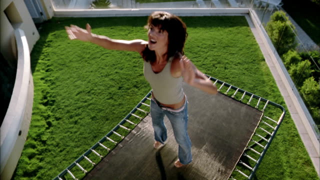 High angle medium shot woman jumping on trampoline in yard