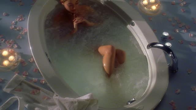high angle medium shot woman lying in hot tub - dressed undressed women stock-videos und b-roll-filmmaterial