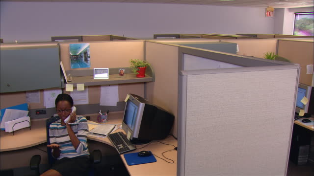 high angle medium shot woman talking on phone at desk / co-worker spying on her over cubicle wall - 盗み聞き点の映像素材/bロール