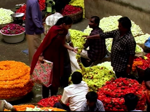 High angle medium shot woman walking through flower market / looking at garlands