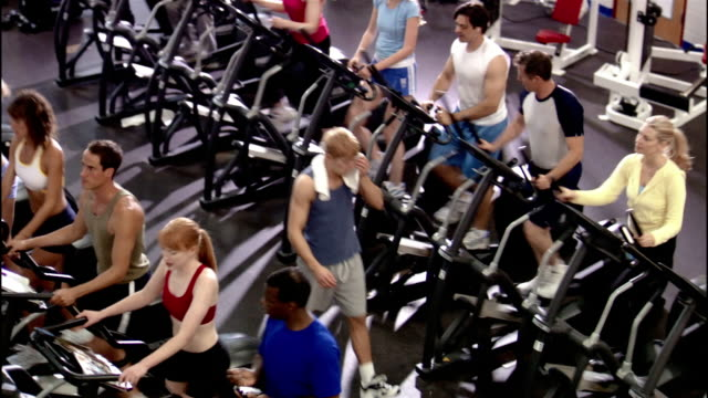 high angle medium shot young man walking between rows of men and women using elliptical trainers / getting on trainer - electronic organiser stock videos & royalty-free footage