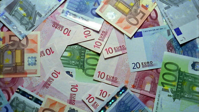 stockvideo's en b-roll-footage met high angle medium shot zoom out pile of euro notes spinning - europese unie