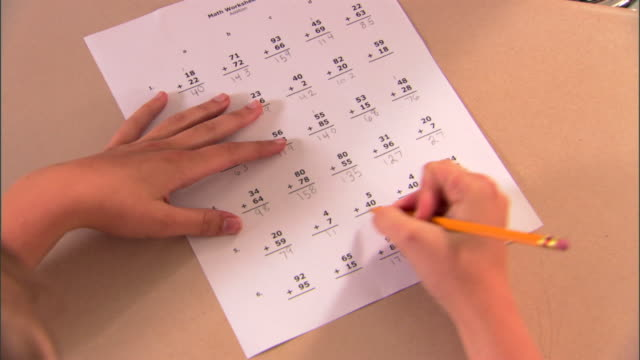 vidéos et rushes de high angle medium view of a student's hands writing answers and corrects mistakes on math problems on a test. - gomme