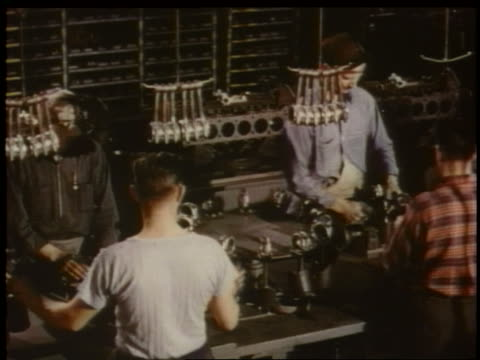 1951 high angle PAN men assembling car parts on assembly line in Chevrolet factory