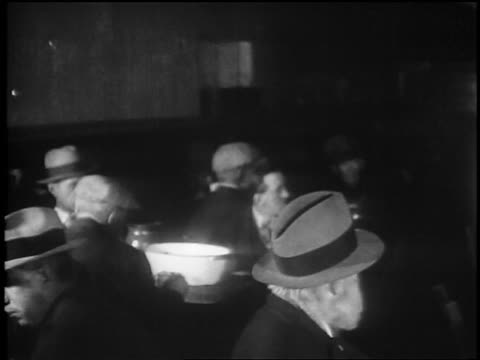 vidéos et rushes de b/w 1929 high angle pan men eating in soup kitchen / great depression / newsreel - tous types de crises