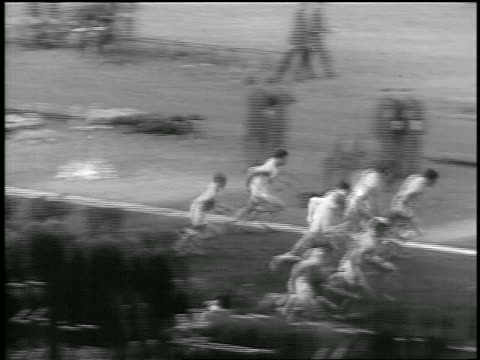 B/W 1933 high angle PAN men taking off from starting line + jumping over hurdles in race / Philadelphia