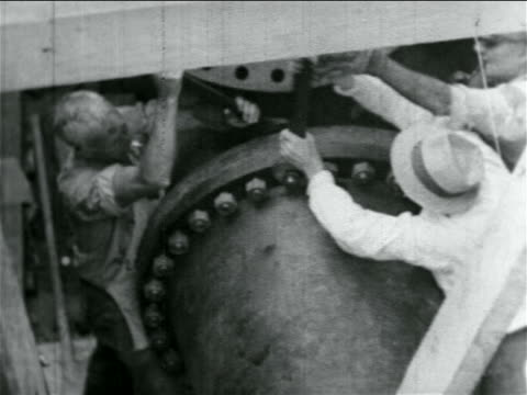 stockvideo's en b-roll-footage met high angle men tightening bolts on large pipes in wpa construction project / documentary - 1934