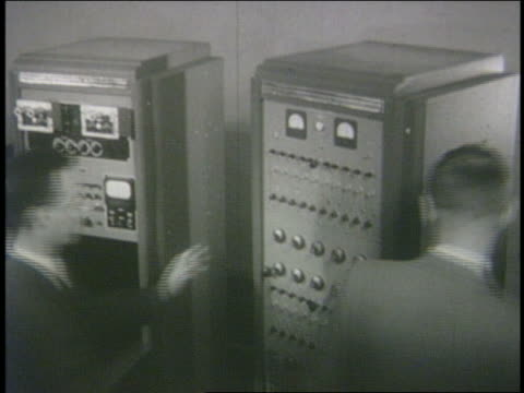 b/w 1950 high angle men turning large computer - 1950年点の映像素材/bロール