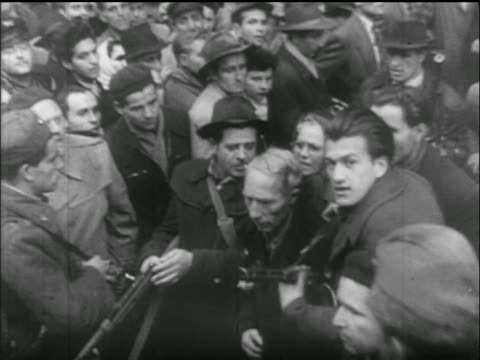 vídeos de stock e filmes b-roll de high angle men with guns pushing through crowd of people / hungarian uprising - 1956