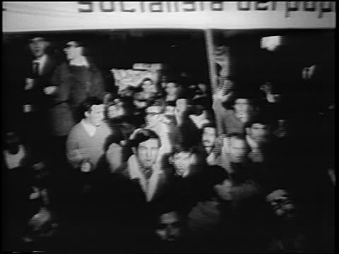 vídeos de stock, filmes e b-roll de b/w 1967 high angle men with socialista dei popoli sign shouting in antiwar rally at night / rome / news - manifestação de paz
