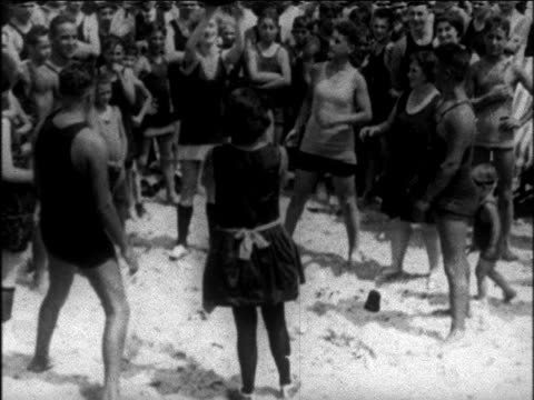 b/w 1925 high angle men + women in swimsuits throwing ball to each other on beach / newsreel - 1925 stock videos & royalty-free footage