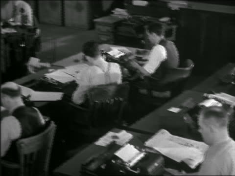 b/w 1949 high angle pan men + women typing + working at desks in newpaper office - press room stock videos & royalty-free footage