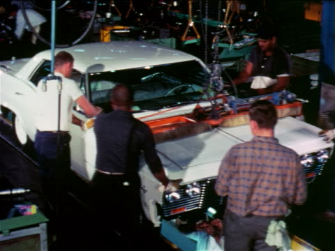 1965 high angle men working on car on assembly line / chevrolet factory / industrial - シボレー点の映像素材/bロール