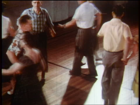 stockvideo's en b-roll-footage met 1957 high angle middle-aged people square dancing indoors / educational - 1957