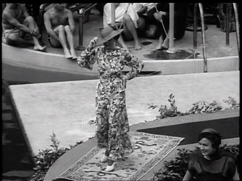vidéos et rushes de b/w 1936 high angle models in gowns turning by pools in outdoor fashion show / miami florida / newsreel - 1936