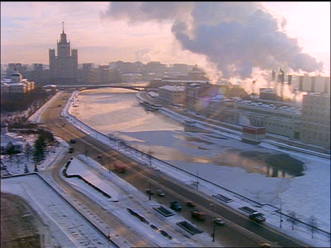 high angle moscow river + factory with smoke billowing from smokestacks in winter / moscow - moscow russia video stock e b–roll