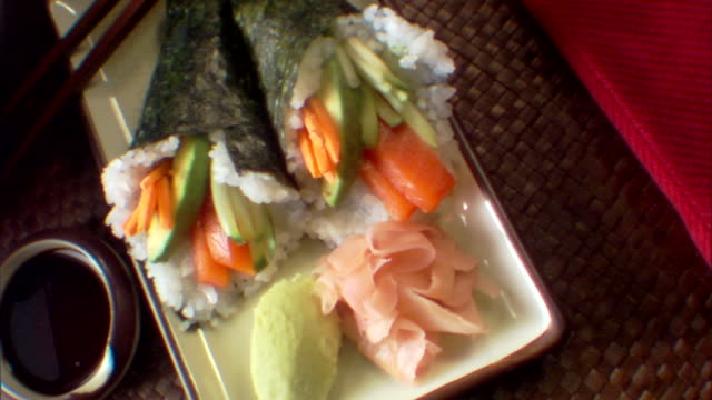 high angle move left over a plate of cone sushi. - wasabi sauce stock videos and b-roll footage