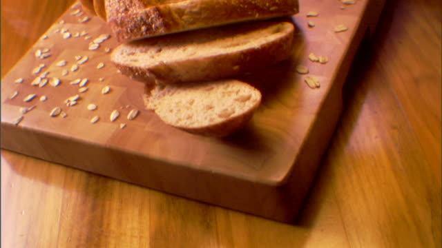 high angle move over a sliced loaf of bread on a cutting board. - loaf of bread stock videos and b-roll footage