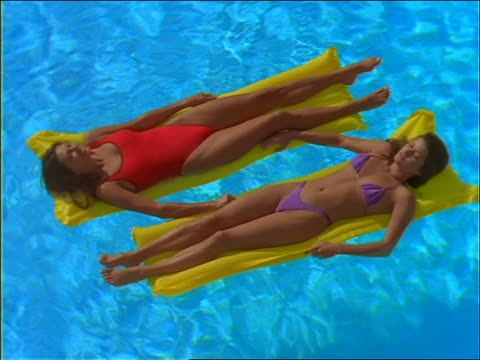 high angle of 2 women in swimsuits lying on rafts in swimming pool