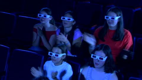 high angle of a group of people clapping while watching a 3d movie. - biosalong bildbanksvideor och videomaterial från bakom kulisserna