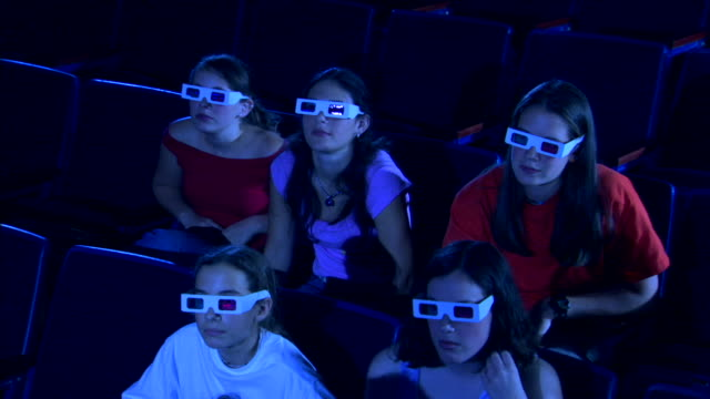 high angle of a group of people leaning in and then jumping back in their seats while watching a 3d movie. - biosalong bildbanksvideor och videomaterial från bakom kulisserna