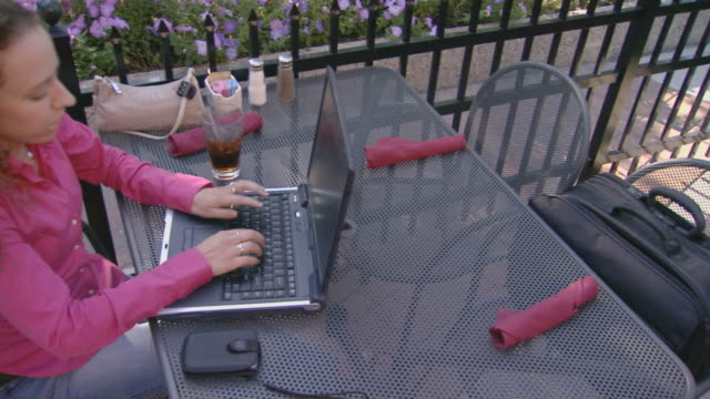 stockvideo's en b-roll-footage met high angle of a teen girl on her lap top computer at an outdoor cafe - 2004