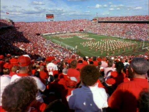 high angle of audience watching marching band on football field - ncaa college football stock videos and b-roll footage