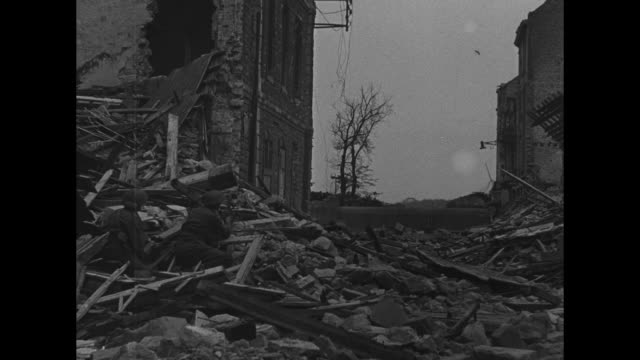 pan high angle of bombed buildings in boulogne france / ls looking down street lined with bombdamaged buildings sole pedestrian walks among the... - francia video stock e b–roll