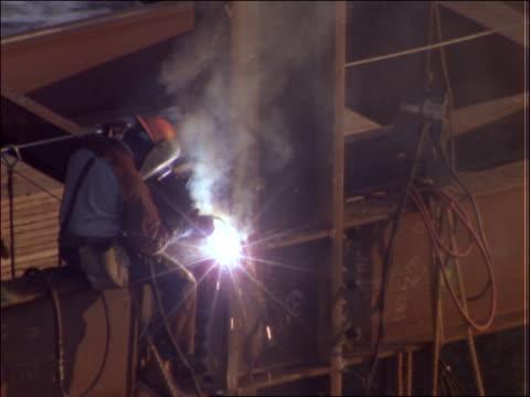 high angle of construction worker welding beams - solo uomini di età media video stock e b–roll