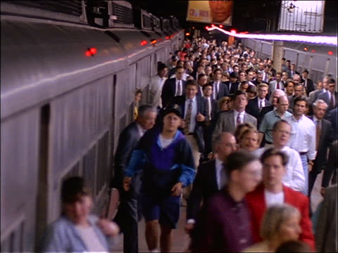 high angle of crowd exiting train onto station platform / NYC