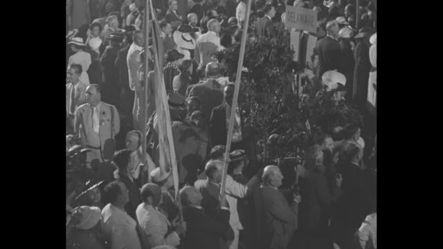 """stockvideo's en b-roll-footage met high angle of crowd on floor of philadelphia convention hall during 1936 democratic national convention, """"minnesota united for roosevelt"""" sign / tree... - graph"""