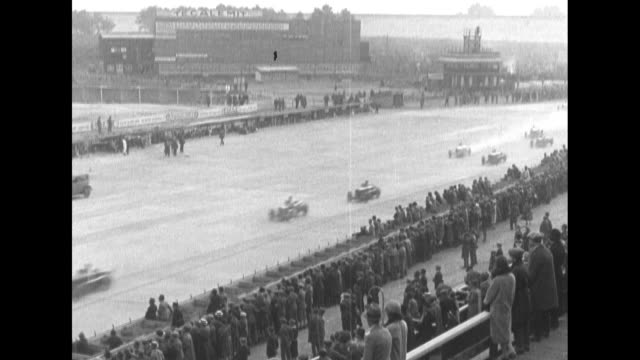 high angle of crowds looking down at racetrack in background as cars pass / mls rear view of cars rounding curve and proceeding away from camera /... - grand prix motor racing stock videos & royalty-free footage