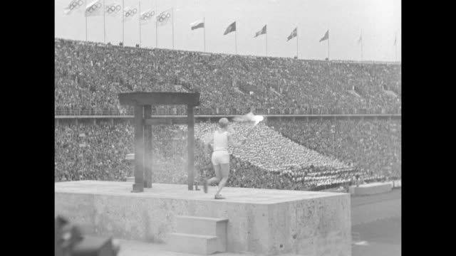 high angle of final torch runner along track inside olympic stadium in opening ceremonies of 1936 berlin games / high angle of torch runner ascending... - 1936 stock-videos und b-roll-filmmaterial