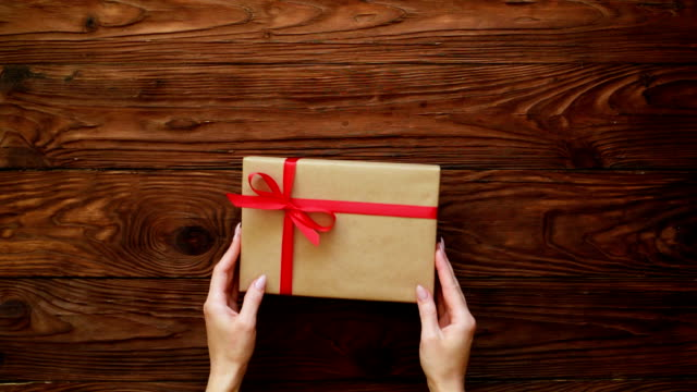 High angle of hands putting a nice present box on a wooden background
