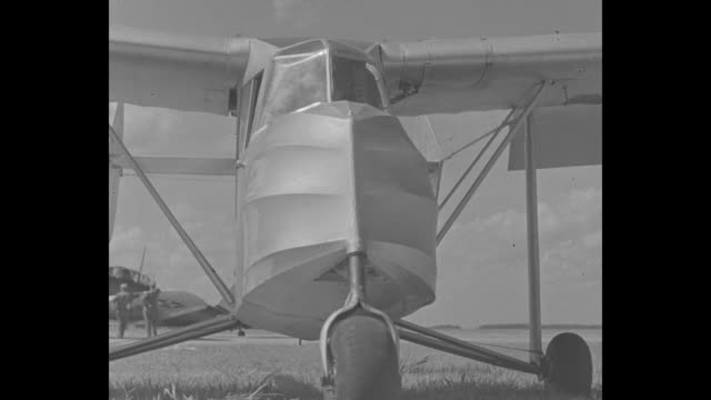 High angle of innovative airplane with inventor Dean Hammond in the pilot's seat manipulating rudders and wings / MS front of plane with Hammond seen...