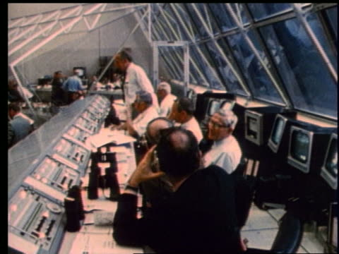 high angle of men at control panels in Mission Control