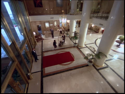 high angle of people walking across floor of hotel lobby / Argentina