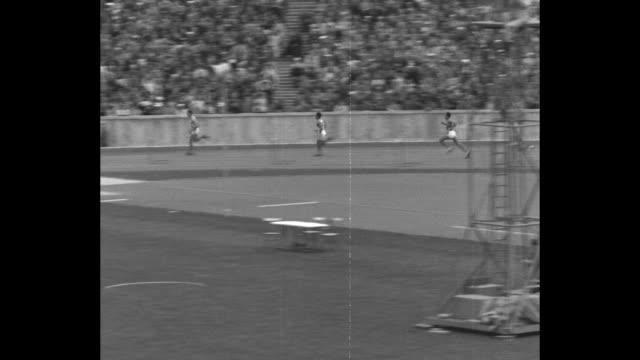 high angle of thousands of spectators in berlin's summer olympics stadium olympiastadion / 8/4/36 800meter race us's john woodruff runs wins / [date... - podio video stock e b–roll