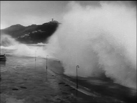 high angle of tidal wave crashing on road of spanish coastal town - tsunami stock videos & royalty-free footage