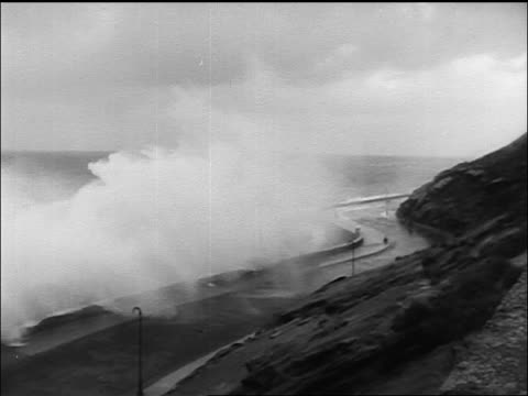 b/w newsreel high angle of tidal wave crashing on road of spanish coastal town - tsunami stock videos and b-roll footage